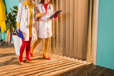 cropped image of retro styled doctors in colorful tights pointing on clipboard in clinic
