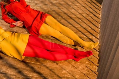 cropped image of girls in colorful tights and dresses lying on floor at home