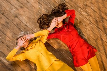 top view of retro styled girls in colorful dresses lying on floor and covering eyes with hands at home