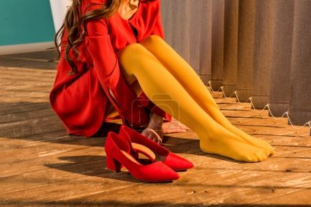 cropped image of retro styled woman in red dress sitting on floor near jalousie at home