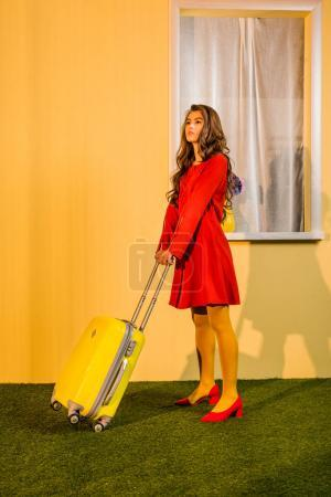 beautiful retro styled woman in red dress standing with bag on wheels at home, travel concept