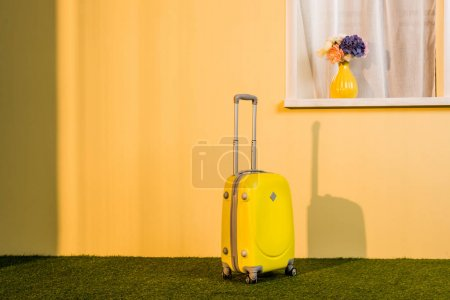 yellow wheeled bag on floor at home, travel concept