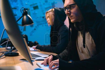 Foto de Par de hackers trabajando con ordenadores para desarrollar nuevo malware - Imagen libre de derechos