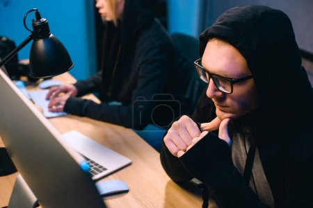 thoughtful young hacker looking at computer screen in dark room