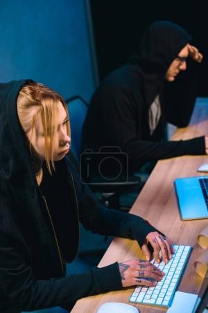 Foto de Vista de ángulo alto de grave mujer hacker trabajando en nuevo malware con cómplice en cuarto oscuro - Imagen libre de derechos