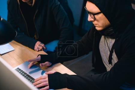Foto de Seria hacker trabajando en nuevo malware con cómplice en cuarto oscuro - Imagen libre de derechos