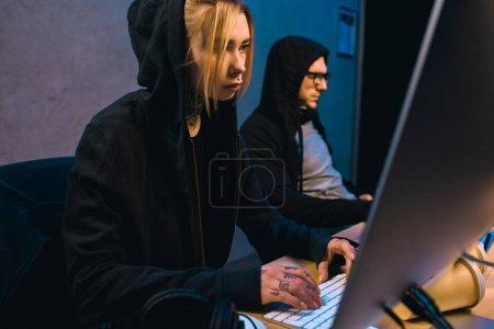 Foto de Grave mujer hacker trabajando en nuevo malware con cómplice en cuarto oscuro - Imagen libre de derechos