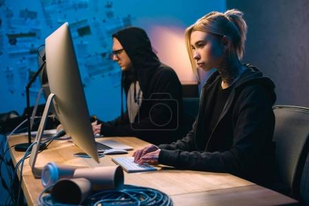 confident couple of hackers working on malware in dark room