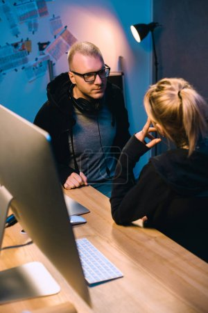 couple of hackers talking to each other at workplace in dark room