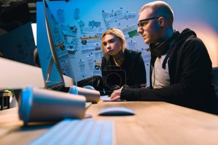 Foto de Reflexivo par de hackers trabajando con computadora en el cuarto oscuro - Imagen libre de derechos