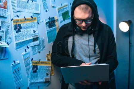 Foto de Joven hacker desarrollar malware con laptop en cuarto oscuro - Imagen libre de derechos