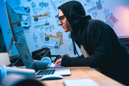 serious hooded hacker working with computer to develop malware