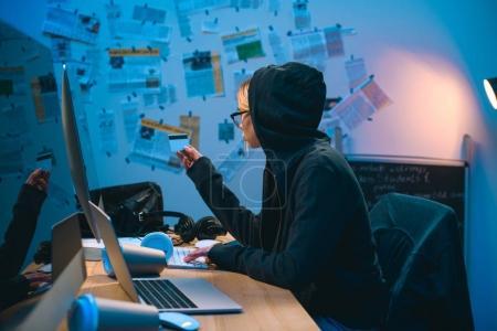 Foto de Mujer hacker con tarjeta de crédito robado trabajando con la computadora - Imagen libre de derechos