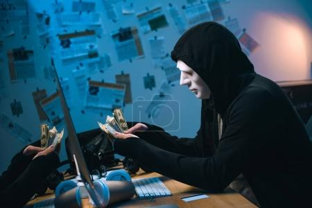 side view of hooded hacker in mask counting stolen money at his workplace