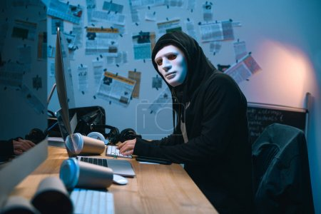 hacker in mask developing malware at his workplace