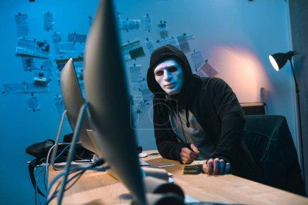 Photo pour Pirate à capuchon dans le masque avec pile d'argent sur le bureau - image libre de droit