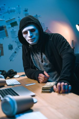 hacker in mask with stack of money on desk