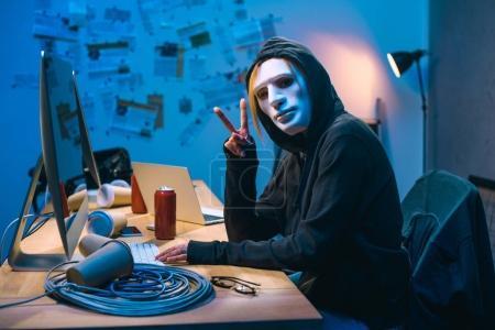 hacker mujer en máscara mostrando v signo en el lugar de trabajo
