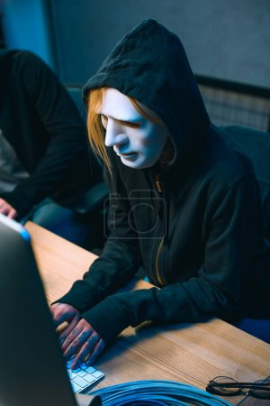 high angle view of hacker in mask working with computer to develop malware