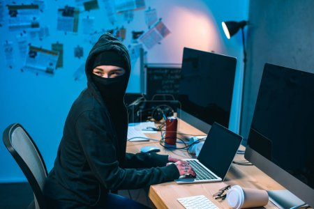 female hacker in mask developing malware at workplace
