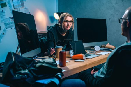 couple of hackers talking at workplace in dark room