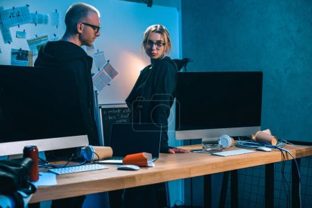 couple of hackers standing near desk with computers in dark room