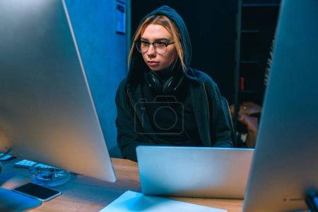 Photo pour Jeune hacker femelle à capuchon développant des logiciels malveillants - image libre de droit
