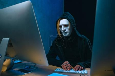 Photo for Masked female hacker developing malware in dark room - Royalty Free Image