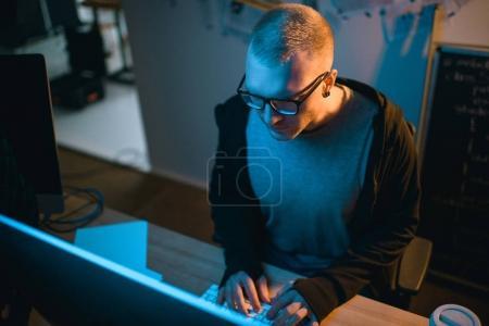 vue grand angle de pirate développant des logiciels malveillants dans la chambre noire