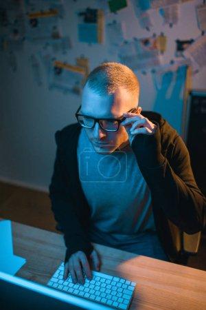 vue grand angle de hacker grave développant des logiciels malveillants dans la chambre noire