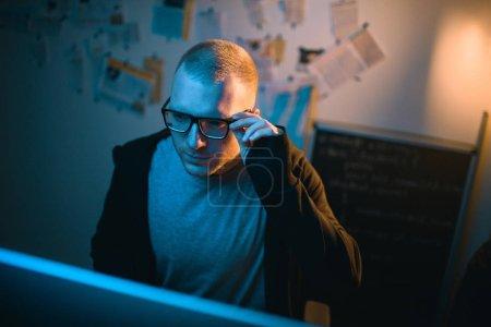 Photo pour Vue grand angle de jeune hacker développant des logiciels malveillants dans la chambre noire - image libre de droit
