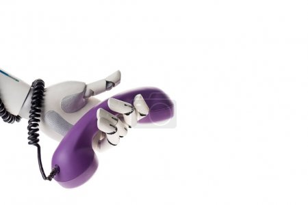 robot hand holding violet stationary telephone handset isolated on white