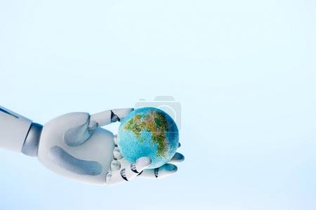 robot hand holding earth model isolated on blue, earth day concept