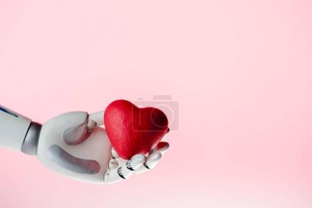 robot hand holding red heart isolated on pink