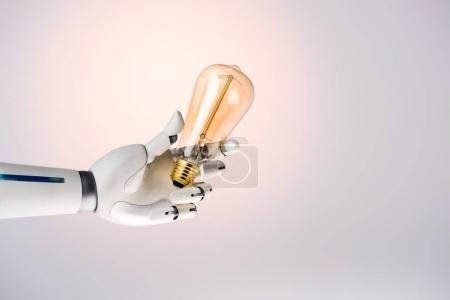robot hand holding yellow lamp isolated on beige