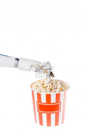 cropped shot of robot taking tasty popcorn out of bucket isolated on white