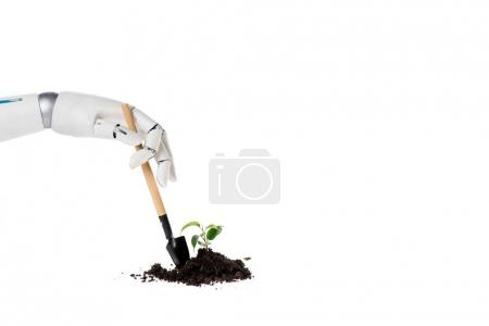 cropped shot of robot shoveling heap of ground with small plant isolated on white