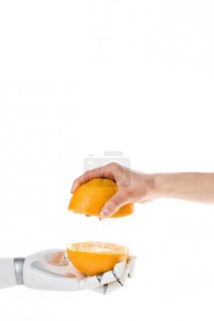 Photo pour Recadrée tir du robot et l'homme avec les moitiés d'orange isolé sur blanc - image libre de droit