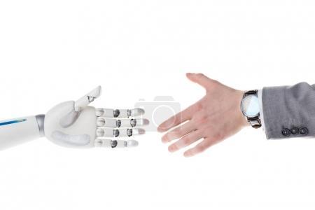 Photo pour Photo recadrée de robot et homme d'affaires atteignant les uns aux autres pour serrer la main isolé sur blanc - image libre de droit
