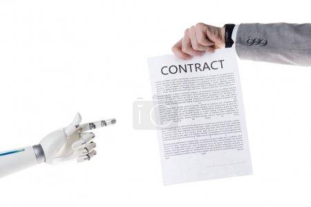 Photo pour Photo recadrée de robot pointant sur les contrats en main de l'homme d'affaires isolé sur blanc - image libre de droit