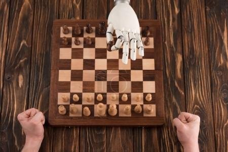 cropped shot of robot playing chess with human on wooden surface