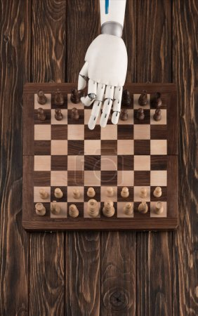 cropped shot of robot playing chess on wooden tabletop