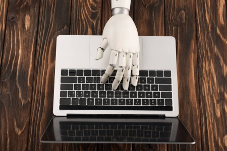 Photo for Cropped shot of robot working with laptop on wooden surface - Royalty Free Image