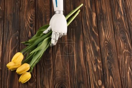 cropped shot of robot holding beautiful bouquet of yellow tulips on wooden surface