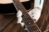 cropped shot of robot playing guitar over wooden surface