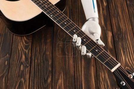 cropped shot of robot playing acoustic guitar over wooden surface