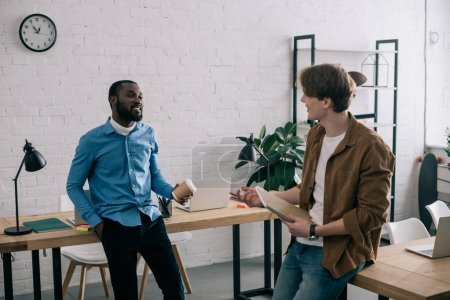 stylish multiethnic business coworkers talking in modern office
