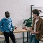 stylish multiethnic business coworkers talking in modern office