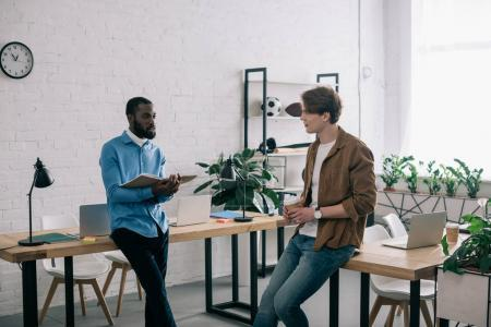 Photo pour Homme d'affaires africain-américain tenant manuel et parler à la collègue de bureau moderne - image libre de droit