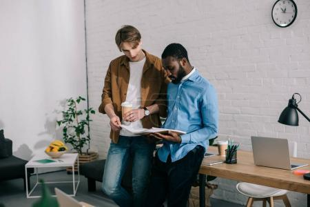businessman with paper cup of coffee watching on textbook and talking to african american coworker